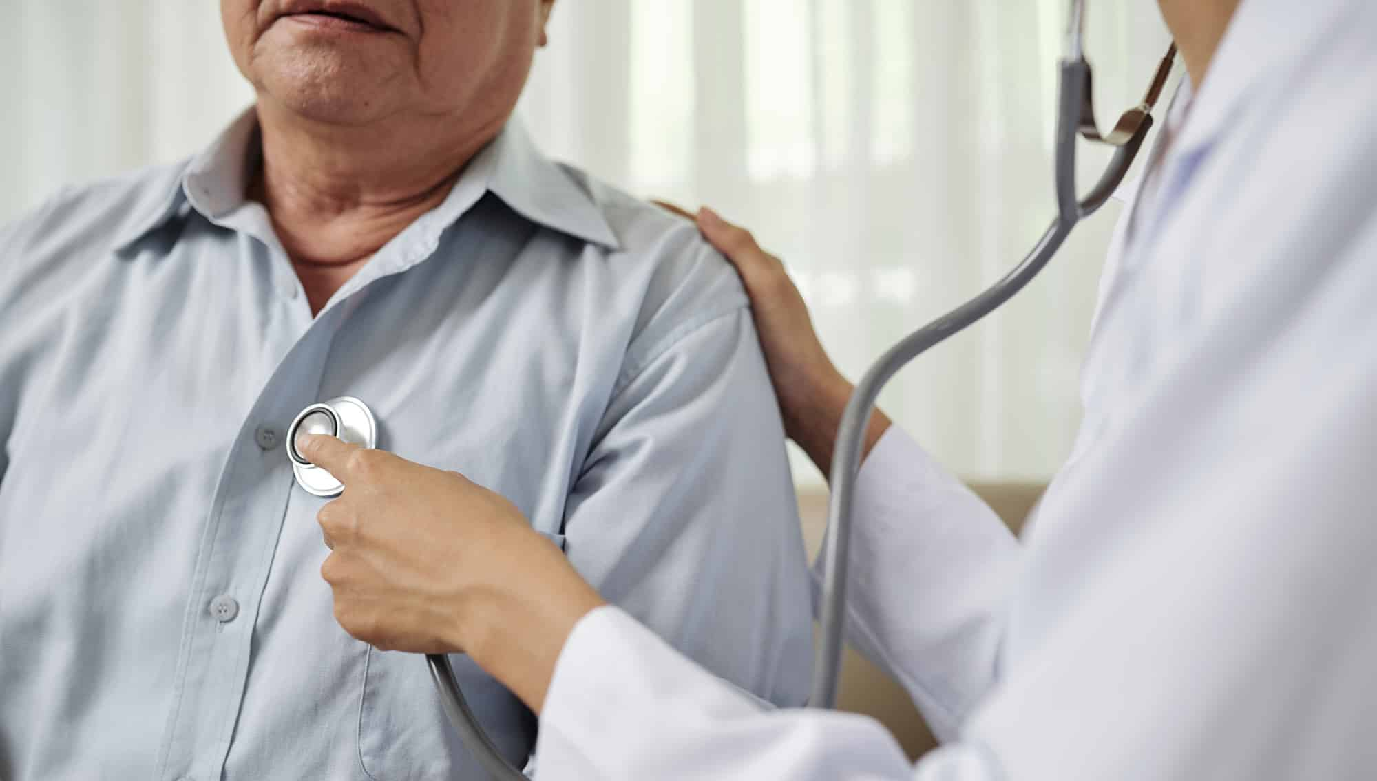 general practitioner checks a patient's heart beat