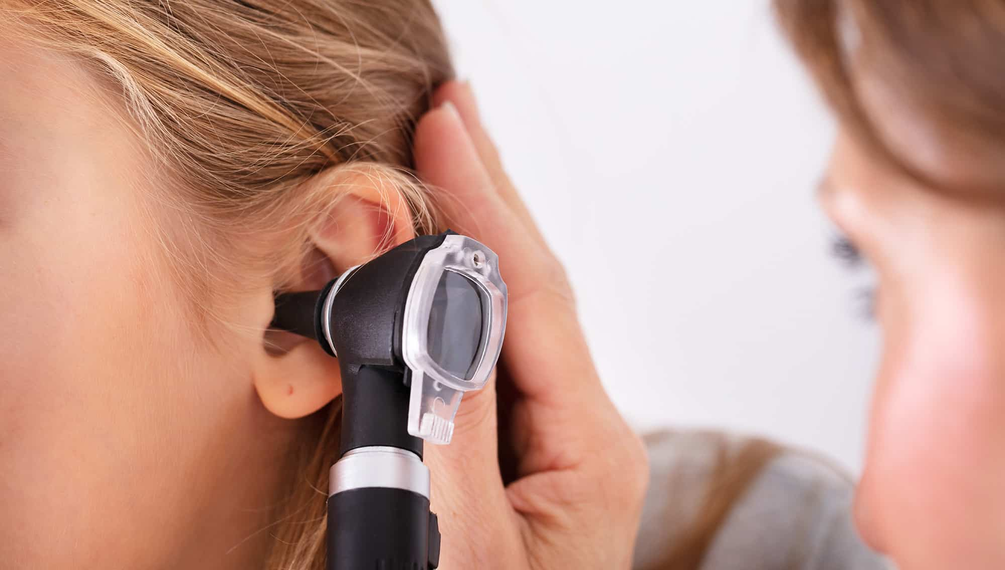 general practitioner checks a patient's ears