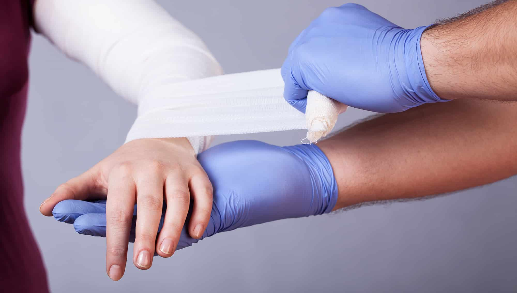 general practitioner wrapping an arm in bandages
